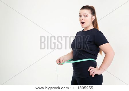 Portrait of a fat woman measuring her waist and looking at camera isolated on a white background