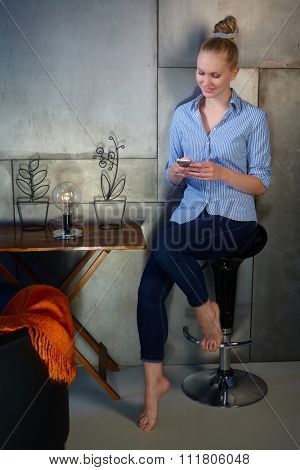 Young woman sitting at home dialing on mobilephone, smiling.