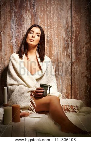 Beautiful sensual woman sitting on floor covered by blanket, looking at camera.