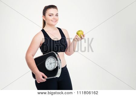 Portrait of a smiling fat woman holding weighing machine and apple isolated on a white background