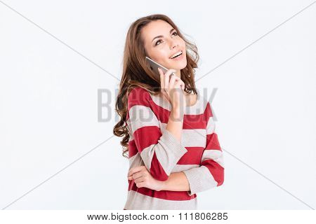 Portrait of a happy thoughtful woman talking on the phone and looking up at copyspace isolated on a white background