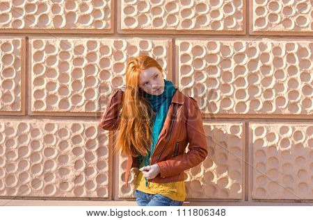 Attractive playful young lady with beautiful long red hair posing in front of the pink brickwall