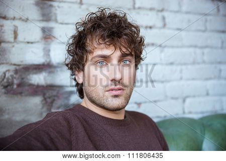 Closeup of attractive thoughtful sad curly male against a brickwall