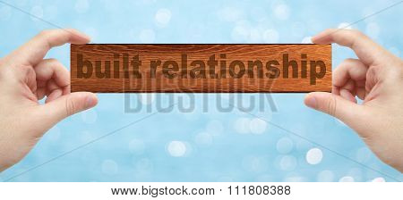 Hands Holding A Wood Engrave With Word Built Relationship