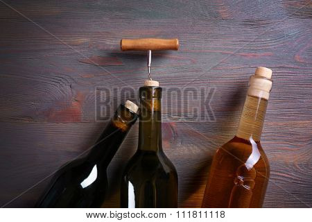 Three bottle wine and corkscrew on wooden background