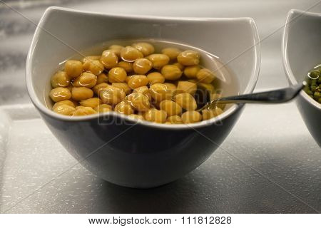 Canned corn and juice in a white bowl, on the table, close-up