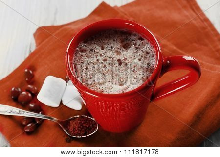 Cup of hot cacao with marshmallow on red cotton serviette, close up