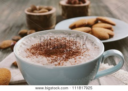 Cup of hot cacao on cotton serviette with cinnamon, almonds and heart shaped cookies, close up