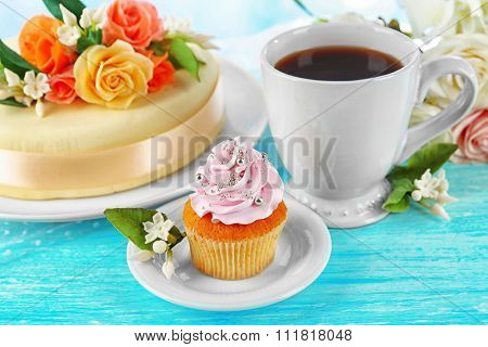 Cake with sugar paste flowers and cupcake, on light background