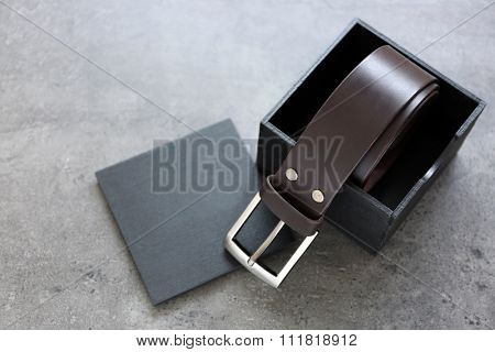 Leather belt with buckle and gift box on gray background