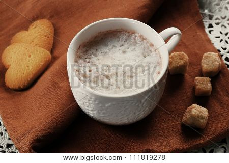 Cup of hot cacao with heart shaped cookies on brown cotton serviette