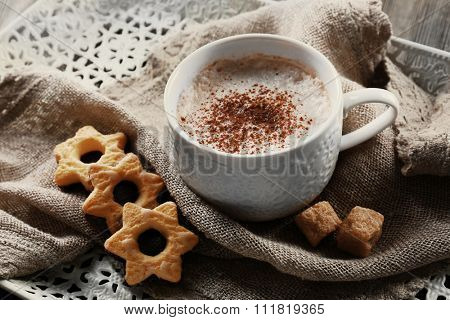 Cup of hot cacao with cookies and nuts on cotton serviette