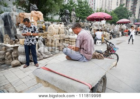 BEIJING - CIRCA JUNE, 2015: Rickshaw Man uses a smartphone while on the famous Panjiayuan Antique Market - one of the best antiques market in China. Area shopping area of 48 500 m2