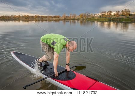 senior male is starting  paddling workout on his stand up paddleboard on a lake in Colorado