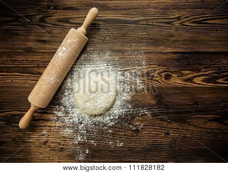Yeast dough on table with rolling pin, shot from above