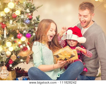 Christmas Family - Father, Mother and little child girl with Holiday Gifts over Decorated Christmas tree. Celebrating New Year. Christmas scene