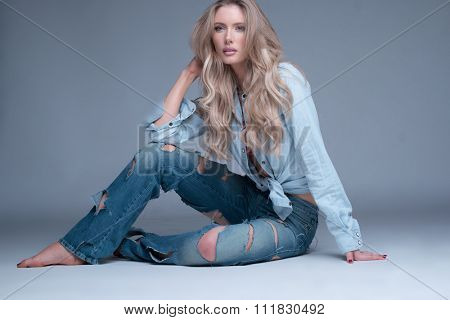 Gorgeous slender young trendy blond woman in slashed designer jeans sitting barefoot relaxing on the floor looking at the camera with a serious expression