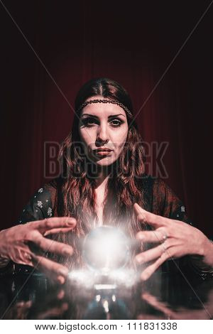Portrait of serious fortune teller using crystal ball against outer space