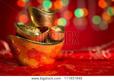 Chinese new year festival decorations, gold ingots on red glitter background.Copy space on side.
