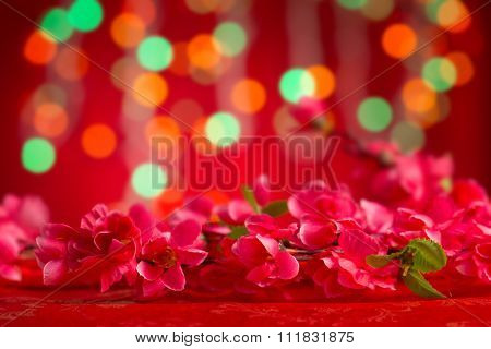 Chinese new year festival decorations, plum flower on red glitter background, copy space on top.