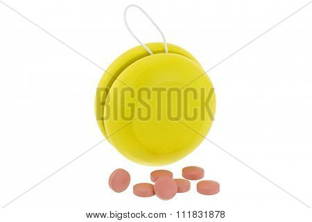 Yellow YoYo next to pink medicines , isolated on white represent the idea of Yo-Yo dieting Effect