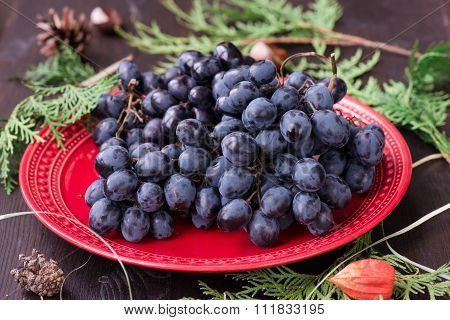 Organic Red Grapes And Fir Branch With Christmas Decorations