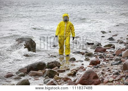 specialist in protective suit with silver suitcase walking on rocky beach in stormy day