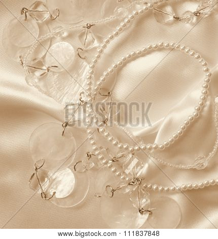 Pearls And Nacreous Beeds On Silk Or Satin As Wedding Background. In Sepia Toned. Retro Style