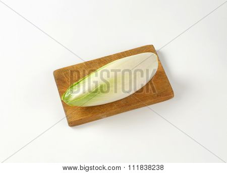 head of fresh belgian endive on wooden cutting board