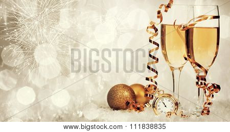 Glasses with champagne and Christmas decoration on sparkling holiday background