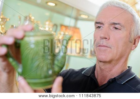 Man looking at antique tea pot