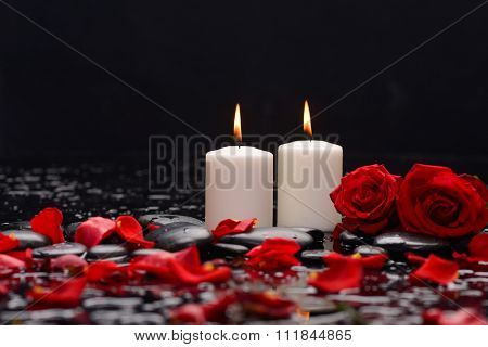 Two Red rose petals with white candle and therapy stones