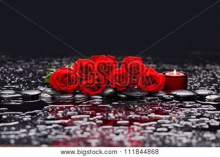 lying on red rose with candle and therapy stones