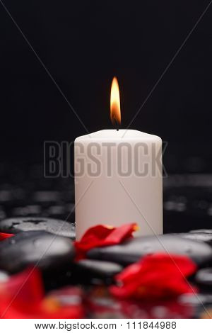 Red rose petals with white candle and therapy stones