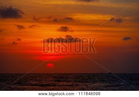 Red Ball Of The Sun Dipping Towards Horizon At Sunset