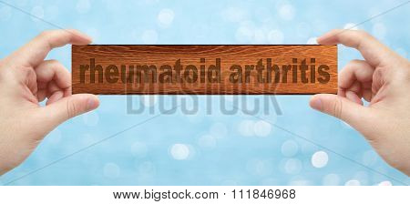 Hands Holding A Wood Engrave With Word Rheumatoid Arthritis