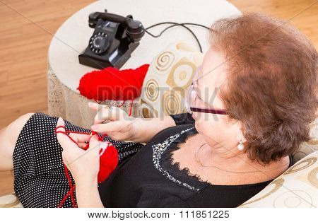 Grandma Sitting Knitting Near The Phone