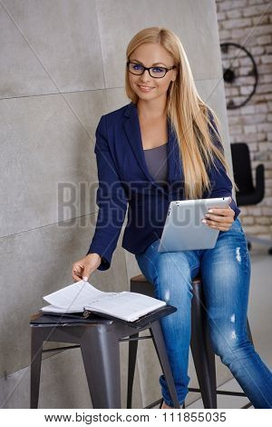 Attractive young woman working with tablet computer, using personal organizer, smiling at camera.