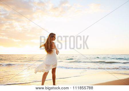 Happy Carefree Woman Enjoying Beautiful Sunset on the Beach