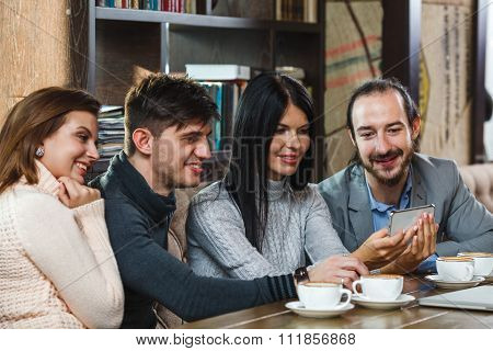 Group of friends in a cafe looking at smartphone