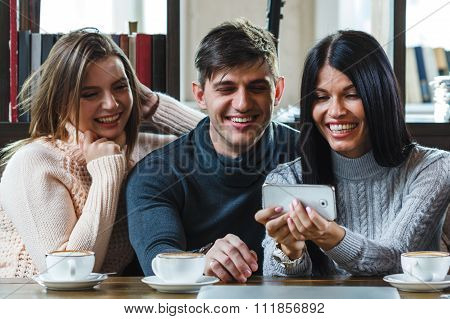 Group of friends ein cafe looking at smartphone