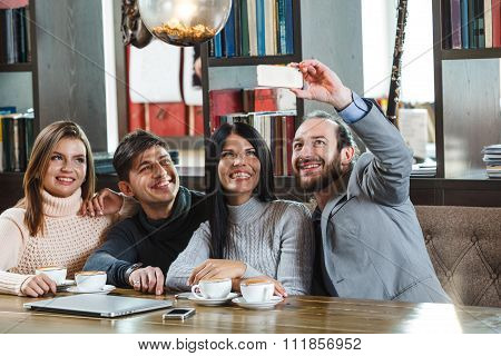 Group of friends in cafe taking photos on smartphone