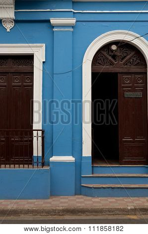 Blue stone wall of colonial house with brown wooden open door in Granada