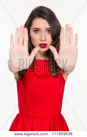 Portrait of a young woman showing stop sign with palms isolated on a white background