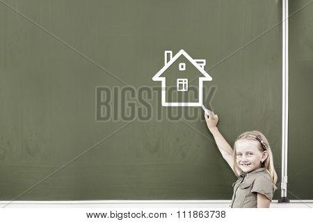 Cute little girl drawing house on blackboard