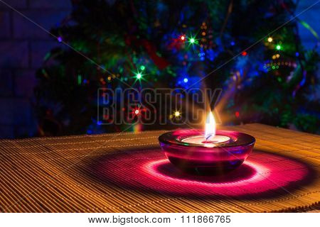 Christmas holiday background with purple candle and colorful lights with copyspace