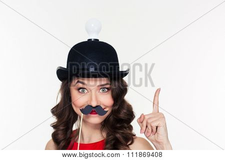 Happy comical young curly girl in amusing black hat with light bulb pointing up and using fake moustache props