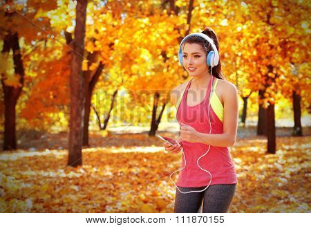 Young beautiful woman running in autumn park and listening to music with headphones.