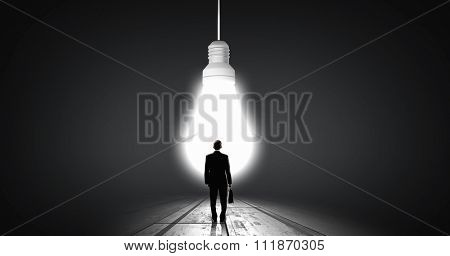 Back view of businessman looking at big glowing light bulb