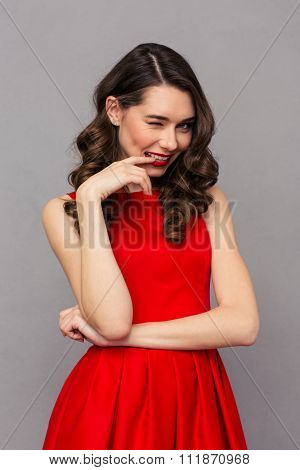 Portrait of a beautiful woman in red dress winking at camera over gray background